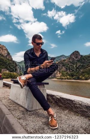 Attractive man using smartphone, stylish guy, black wear, hand watch, pretty, attractive, tan, man in sunglasses, black shirt, casual, fashion #1237196323