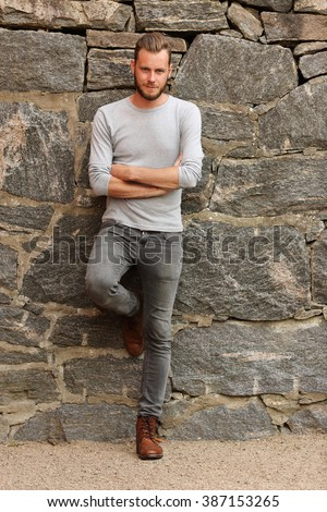 Attractive man wearing a grey sweater standing in front of a wall outside on a sunny summer day.