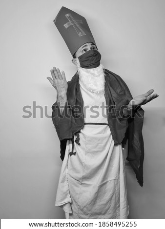 attractive man wearing saint nicholas costume and face mask to protect from coronavirus. celebrating winter holidays in 2020. boy gesturing near white wall. Stock photo ©