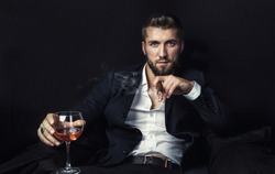 Attractive man with a cigar, and a glass of wine in his hands