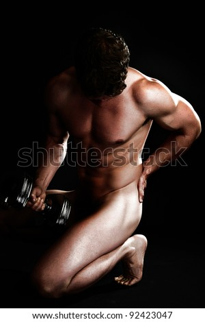Attractive Man with Dumbbell Hand Weights Nude Over Black Background