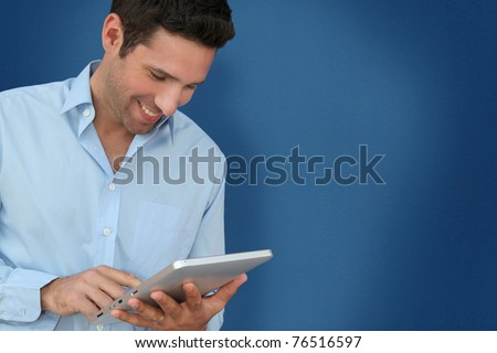 Attractive man with touchpad on blue background