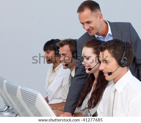 Attractive manager checking his young team work in a call center