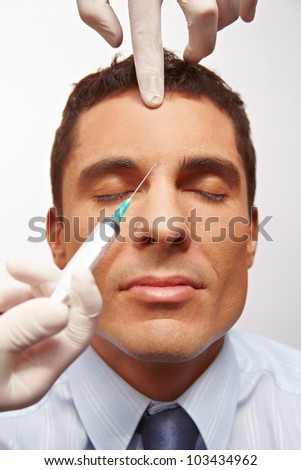 Attractive manager getting needle in forehead for wrinkle removal