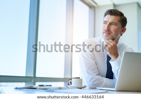 Attractive mature business executive with a stylish short beard, sitting at his office desk and looking out of his window with a thoughtful and optimistic expression