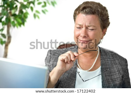 Attractive mature businesswoman looking with dismay, disbelief or amusement at her computer