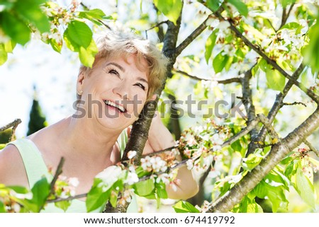 Attractive mature woman embracing nature. Grandmother smiling and spending time in a summer garden. #674419792