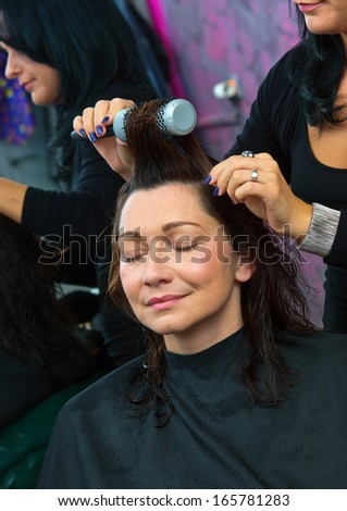 attractive mature woman in hair salon making new haircut by hairdresser