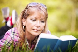Attractive mature woman reading a book in the park.Moment of leisure.