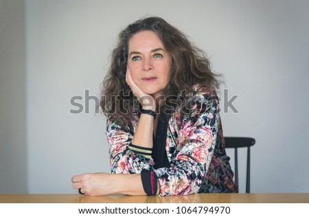 Attractive mature woman sitting deep in thought daydreaming as she rests her chin on her hand staring up with a faraway expression