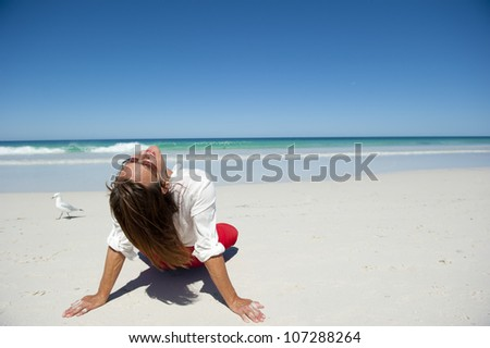 Attractive mature woman sitting in seductive pose and happy relaxed at tropical beach paradise, isolated with ocean and blue sky as background and copy space.