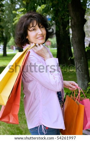 Attractive mature woman standing and holding   Shopping Bags
