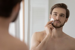 Attractive metrosexual guy cleansing face with cotton disc, rubbing facial skin with sponge. Handsome man applying cream, lotion at mirror, refreshing complexion. Male beauty care, skincare concept