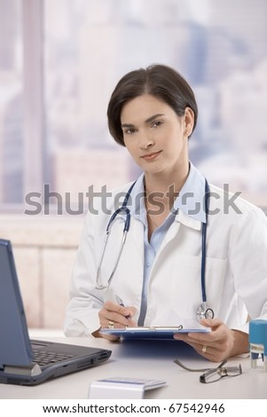 Attractive mid-adult female doctor sitting at desk in office doing paperwork, looking up and smiling at camera.?
