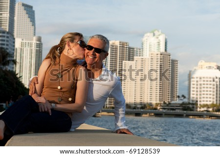 Attractive middle age couple posing along the bay front with condos in the background.