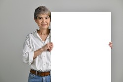 Attractive middle aged Asian woman holding blank signboard isolated on white background. looking at the camera