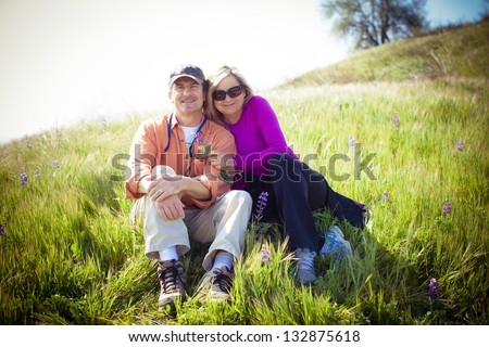 Attractive Middle aged couple lying in the tall grass and Wild Lupine