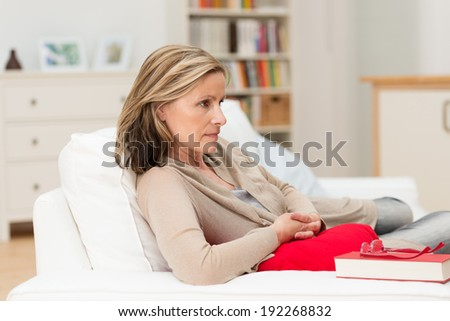 Attractive middle-aged depressed worried woman relaxing at home lying on a sofa staring straight ahead with a serious expression