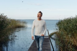 Attractive middle-aged man posing on a jetty between tall reeds on a tranquil lake or ocean looking off to the side as he walks towards the camera