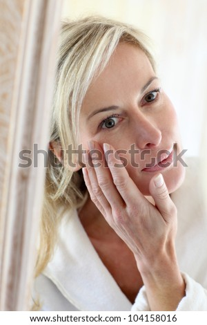 Attractive middle-aged woman applying comestics on her face