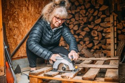 attractive middle aged woman cuts the wood with a circular saw, cutting wood for the fireplace, shed with wood