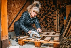 attractive middle aged woman cuts the wood with a circular saw, cutting wood for the fireplace. DIY