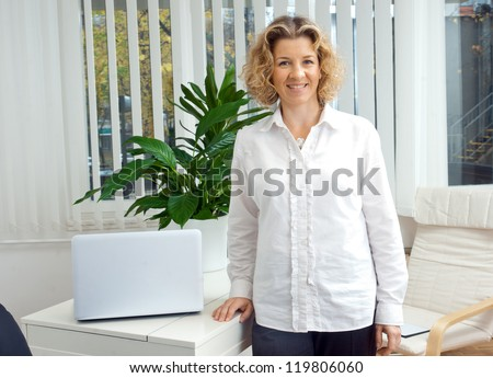 attractive middle aged woman in her office