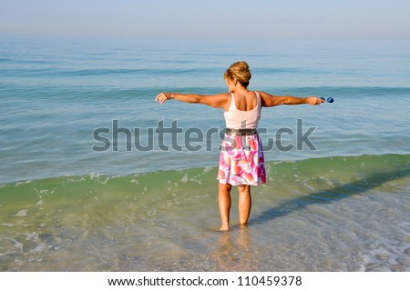Attractive Middle Aged Woman Standing in the Ocean Holding Her Arms Out