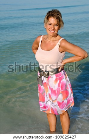 Attractive Middle Aged Woman Standing in the Ocean Surf