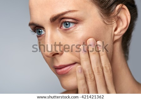 Shutterstock Attractive middle aged woman touching her cheek skin, mature beauty concept