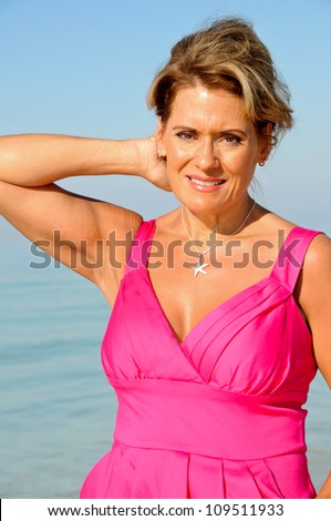 Attractive Middle Aged Woman Wearing A Pink Summer Dress on the Beach