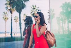Attractive millennial female tourist in stylish sunglasses using roaming megabytes for making operator call to customer service solving problems with internet connection, beautiful woman phoning