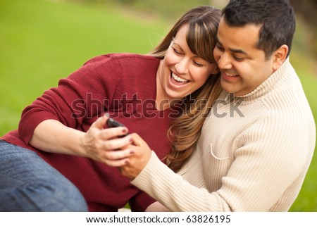 Attractive Mixed Race Couple Enjoying Their Camera Phone in the Park.
