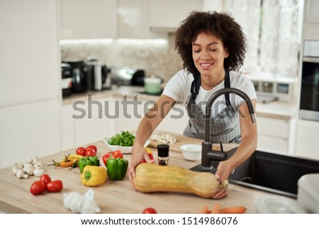 Attractive mixed race woman in apron taking zucchini from kitchen counter. On kitchen counter are lots of vegetables.