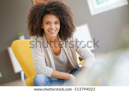 Attractive mixed race woman sitting in yellow armchair