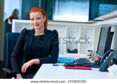 attractive modern businesswoman sitting and talking to phone in office cubicle workstation