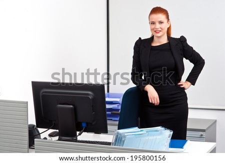 attractive modern red hair businesswoman  in small office cubicle workstation
