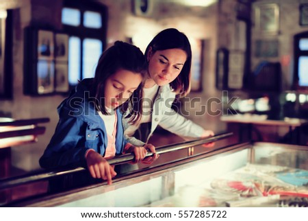 Attractive mother and daughter exploring expositions of previous centuries in museum. Focus on the woman