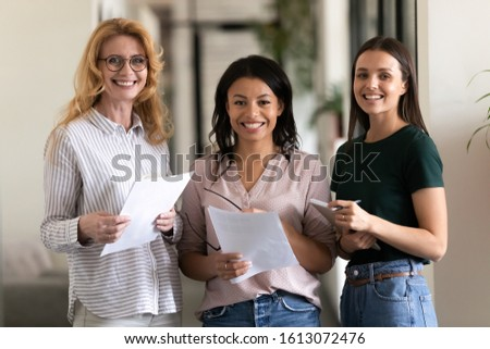 Attractive multi-ethnic businesswomen different age and ethnicity women colleagues posing standing in office hallway prepared for negotiations or presentation holding documents notepad feels confident