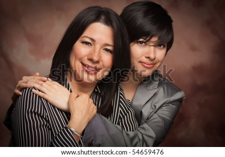 Attractive Multiethnic Mother and Daughter Studio Portrait on a Muslin Background.