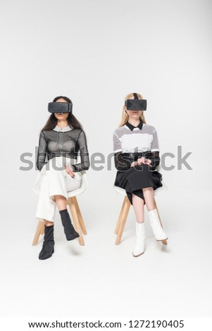 attractive multiethnic women in virtual reality headsets sitting on chairs isolated on white