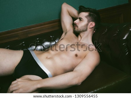 Attractive muscle guy posing with black briefs on leather sofa.