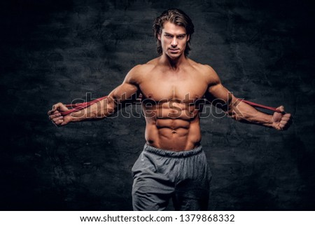 Attractive muscular man is looking to the camera while doing stretchening with rubber.