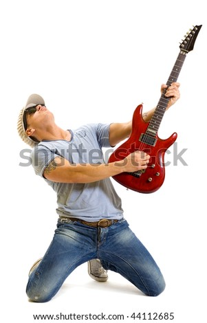 Attractive musician playing guitar on his knees over white