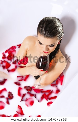 Attractive naked girl enjoy a glass of wine in bath with milk and rose petals. Spa treatments for skin rejuvenation and full relaxation