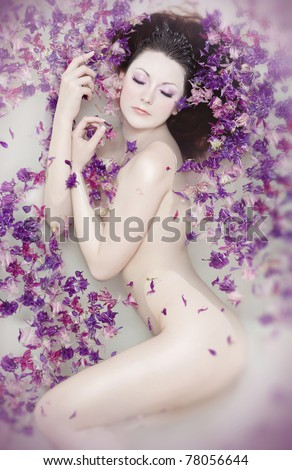 Attractive naked girl enjoys a bath with milk and rose petals Spa treatments for skin rejuvenation