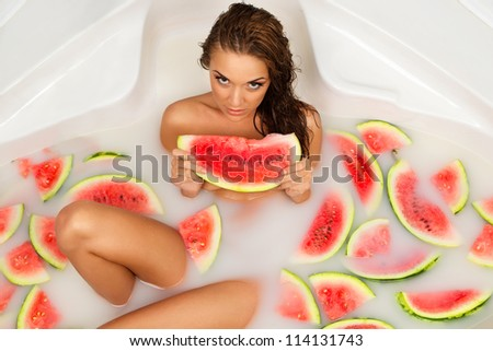 Attractive naked girl enjoys a bath with milk and slices of watermelon.