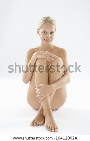 Attractive naked woman isolated on a white background, smiling at camera.