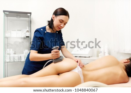 Attractive naked woman lying and enjoying procedure in modern beauty salon. Professional cometologist doing anticellulite massage on buttocks using vela shape, preventing overweight. #1048840067