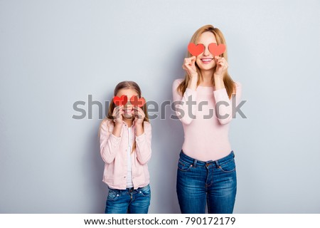 Attractive, nice, cute, sweet, charming daughter and mom, mum standing over gray background, holding four small paper hearts on eyes place, smiling, having fun #790172179